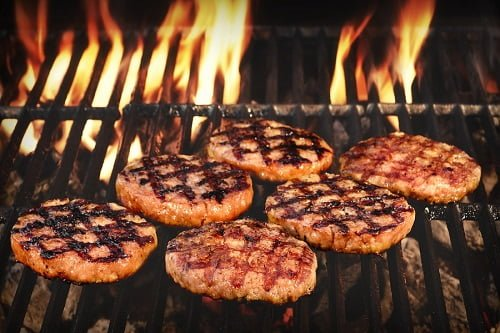 BBQ Grilled Burgers Patties On The Hot Flaming Charcoal Grill Top View. Cookout Food Good Snack For Outdoor Party Or Picnic