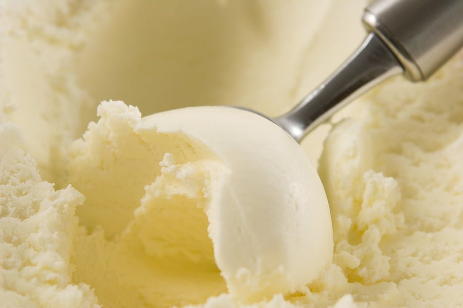 Close up of a scoop filled with vanilla ice cream