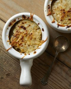 Two bowls of french onion soup on a wooden table